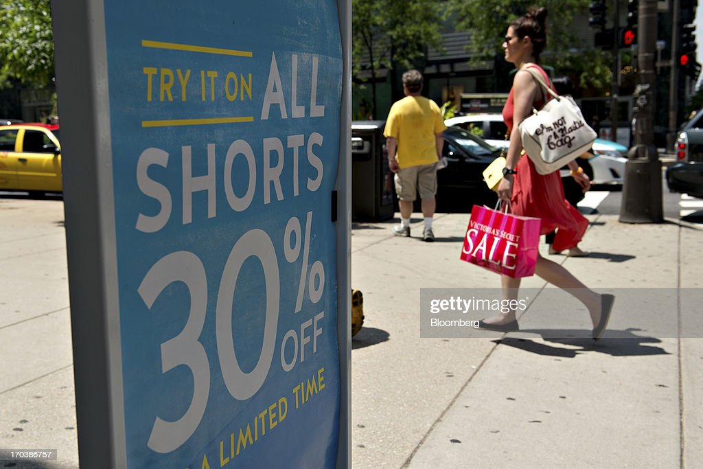 A shopper passes a sign outside a Gap Inc. store in a retail area known as the 'Magnificent Mile' in Chicago, Illinois, U.S., on Tuesday, June 11, 2013. Sales at U.S. retailers probably rose in May as an improving job market gave consumers the confidence to shop for automobiles, home furnishings and clothing, economists said before reports this week. Photographer: Daniel Acker/Bloomberg via Getty Images