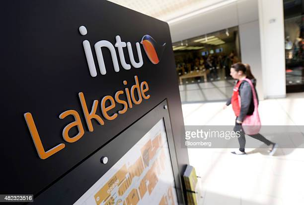 Shopper passes an information board at Lakeside shopping centre, operated by Intu Properties Plc., in Thurrock, U.K., on Wednesday, July 2015. U.K....