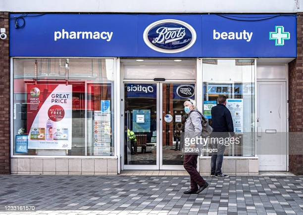 Shopper passes by Boots Beauty Pharmacy on Bow St.