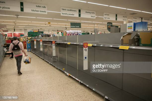 Shopper passes Empty toilet roll shelves inside a Morrisons supermarket in the centre of York, northern England, on March 19, 2020. - Britain's...