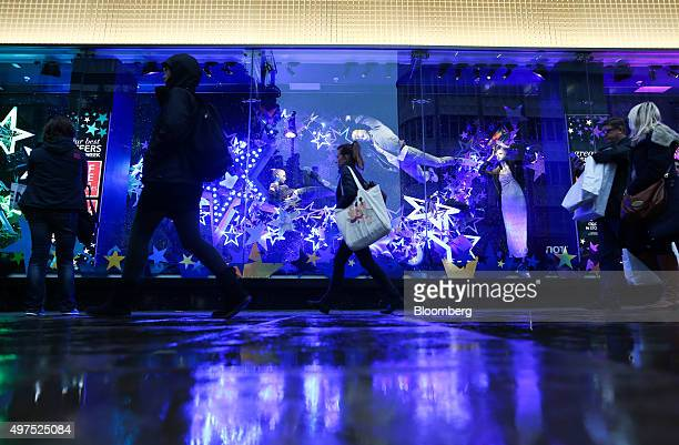 A shopper passes the Christmas window display in the Debenhams Plc department store on Oxford Street in London UK on Tuesday Nov 17 2015 UK consumer...