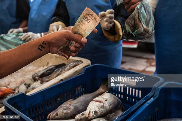 A shopper pays a vendor for fish in Caracas Venezuela on Saturday Feb 6 2016 The person's place in line is written on their wrist Galloping inflation...