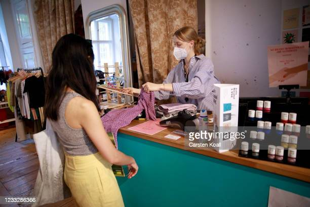 Shopper pays for clothes in a store on the second day that people are no longer required to show a negative Covid test result to enter non-essential...