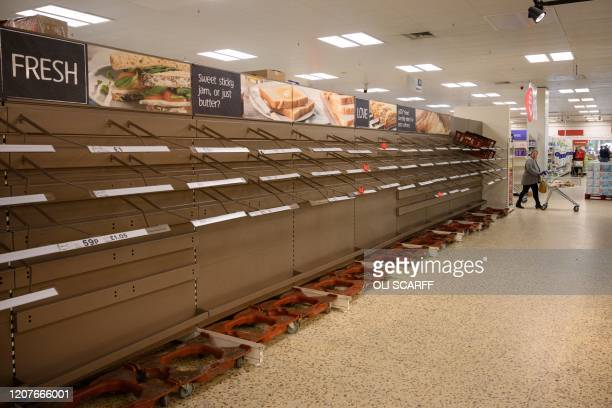 Shopper peruses near-empty bread shelves at a supermarket in the centre of York, northern England, on March 19, 2020. - Britain's supermarkets on...