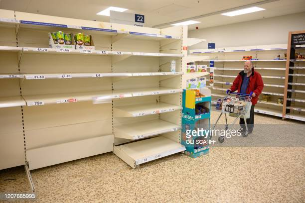Shopper peruses near-empty shelves at a supermarket in the centre of York, northern England, on March 19, 2020. - Britain's supermarkets on Wednesday...