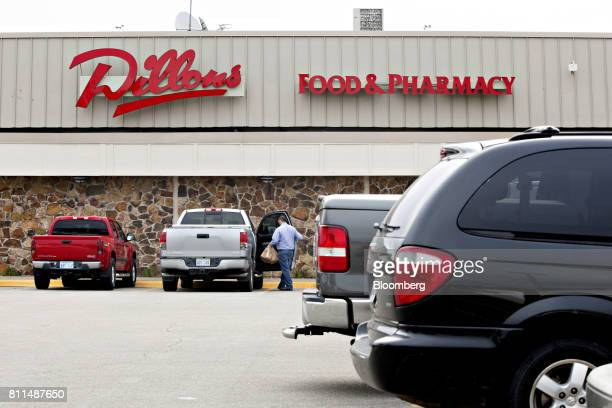 A shopper places grocery bags into a vehicle outside of a Dillons Food Stores supermarket owned by Kroger Co in Hays Kansas US on Thursday June 29...