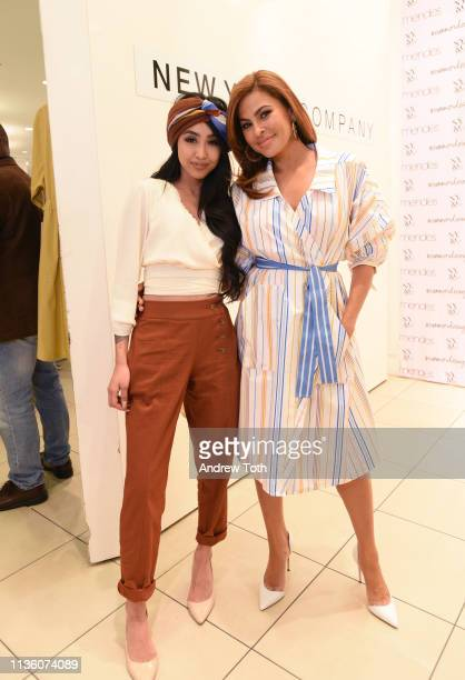 A shopper poses with Eva Mendes as she visits New York Company Store on March 15 2019 in Burbank California