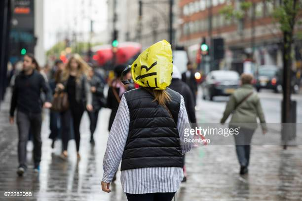 A shopper protects her hair from the rain with a shopping bag on Oxford Street in central London UK on Monday April 24 2017 UK consumer confidence...