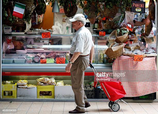 A shopper pulls a shopping cart past a meat and cheese stall inside an indoor market in Rome Italy on Tuesday Aug 12 2014 Italy's economy shrank 02...