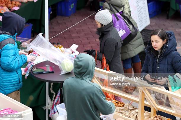 A shopper purchases goods at the Safe Supply outdoor grocery store at Bow Market on March 21 2020 in Somerville Massachusetts In order to comply with...