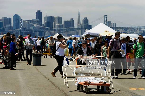 A shopper pushes a cart with items purchased at the Alameda Point Antiques Faire in Alameda California US on Sunday Aug 4 2013 The Bloomberg Consumer...