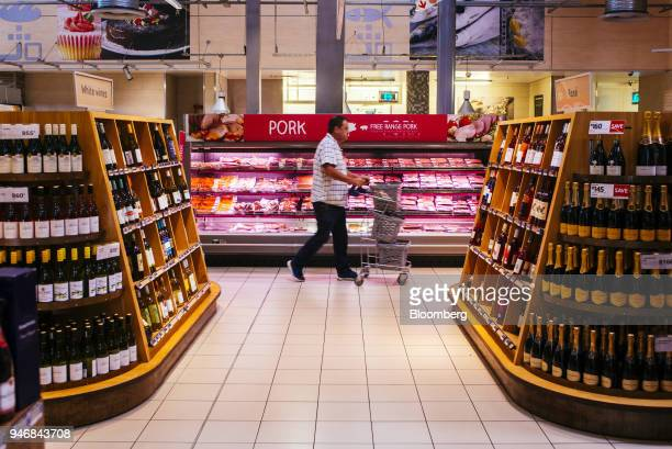 A shopper pushes a shopping cart past shelves displaying bottles of wine inside a Pick n Pay Stores Ltd supermarket in Johannesburg South Africa on...
