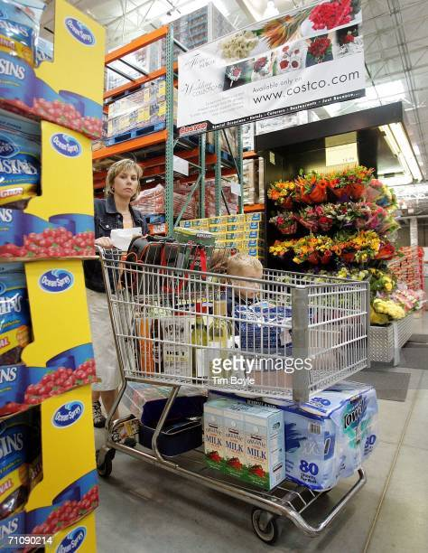 A shopper pushes her cart in a Costco Wholesale store May 31 2006 in Mount Prospect Illinois Thirdquarter earnings reported today were up at Costco...