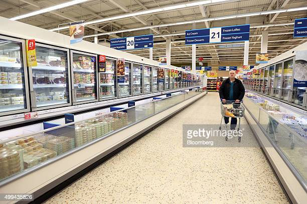 A shopper pushes his shopping trolley through the frozen products aisles at the Tesco Basildon Pitsea Extra supermarket operated by Tesco Plc in...