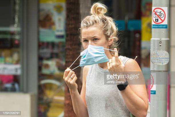 Shopper removes her mask after leaving a supermarket in Manly on January 03, 2021 in Sydney, Australia. Face masks are now compulsory in certain...