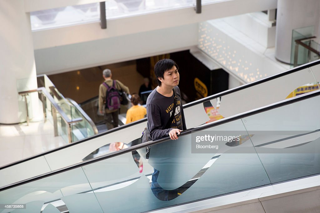 A shopper rides an escalator at Lok Fu Plaza, operated by the Link Real Estate Investment Trust (REIT), in Hong Kong, China, on Monday, Nov. 10, 2014. The Link REIT, Asia's largest property trust which owns neighborhood malls, food markets, and car parks, is scheduled to announce interim results on Nov. 13. Photographer: Brent Lewin/Bloomberg via Getty Images