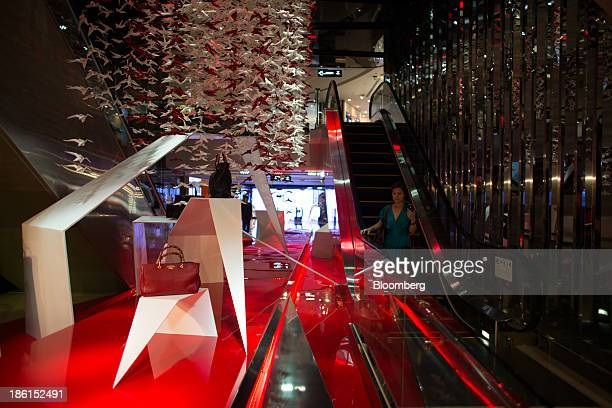 A shopper rides an escalator in the DFS Group Ltd T Galleria store in the shopping district of Tsim Sha Tsui in Hong Kong China on Monday Oct 28 2013...