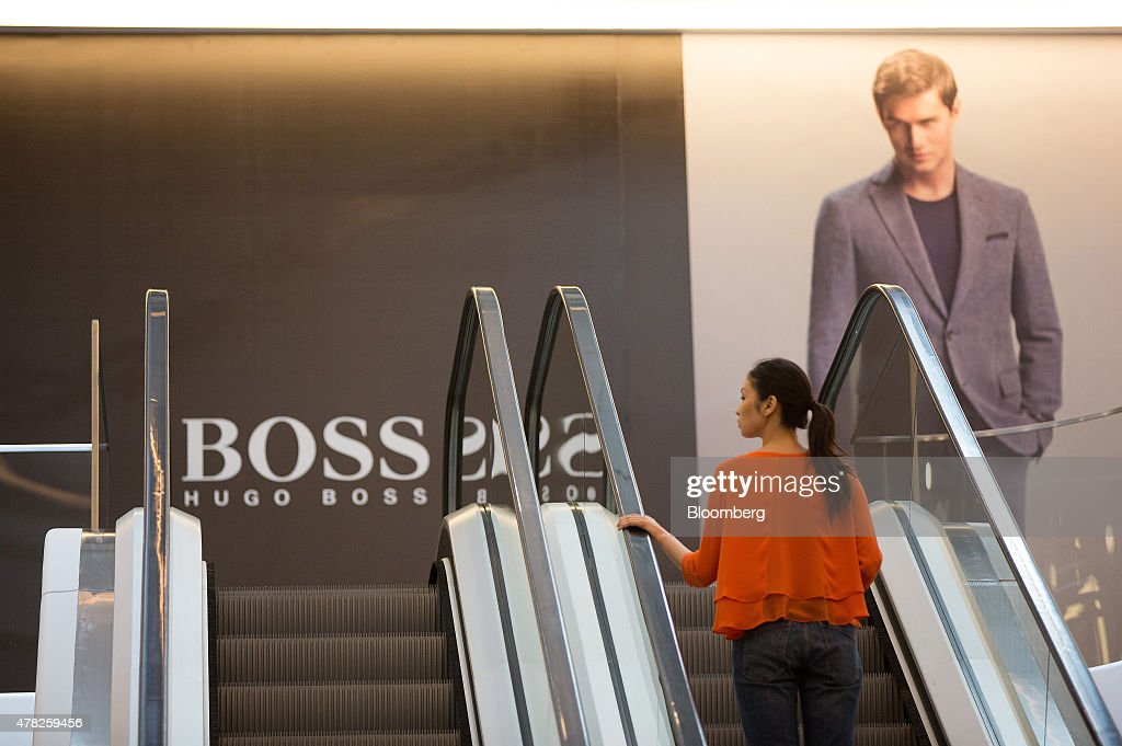 A shopper rides an escalator near a Hugo Boss AG advertisement for men's fashions at the Esentai luxury shopping mall in Almaty, Kazakhstan, on Tuesday, June 23, 2015. Kazakhstan completed its negotiations to become the 162nd member of the World Trade Organization, after 19 years of negotiations, and hopes to fully ratify its accession by Oct. 31. Photographer: Andrey Rudakov/Bloomberg via Getty Images