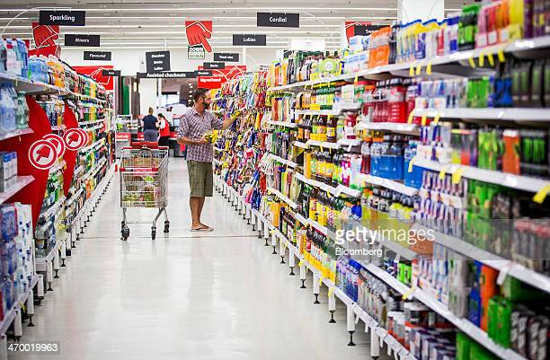 A shopper selects produts in an aisle inside a Coles supermarket operated by Wesfarmers Ltd in Sydney Australia on Tuesday Feb 18 2014 Wesfarmers...