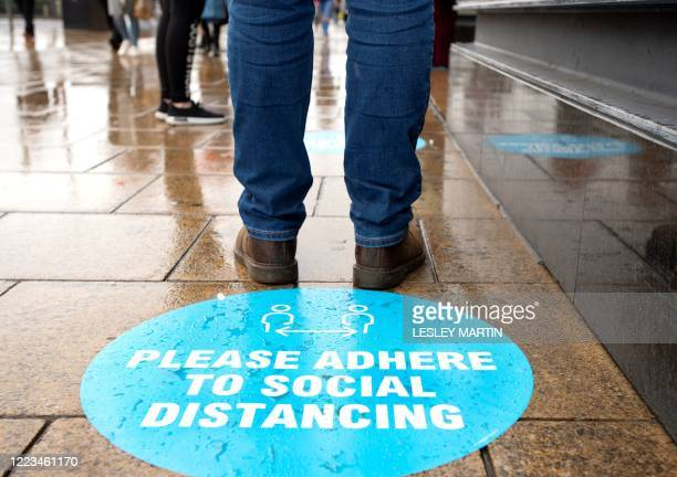 A shopper stands by a pavement sticker asking people to adhere to social distancing measures as they queue to enter a shop on Princes Street in...