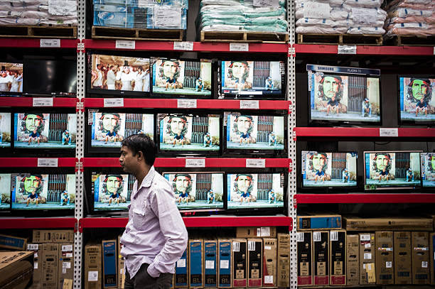 A shopper stands in front of flat screen televisions for sale at a Bharti Walmart Pvt Ltd Best Price Modern Wholesale store in Zirakpur on the...