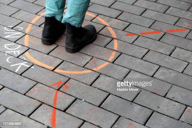 A shopper stands in the on deck circle at the Safe Supply outdoor grocery store at Bow Market on March 21 2020 in Somerville Massachusetts In order...