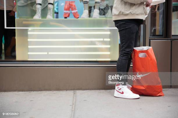 A shopper stands next to a Nike Inc retail bag on the sidewalk in the SoHo neighborhood of New York US on Friday Feb 9 2018 Bloomberg is scheduled to...