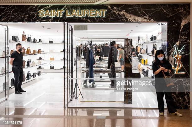 Shopper stands outside the French luxury fashion brand Yves Saint Laurent store seen in Hong Kong.
