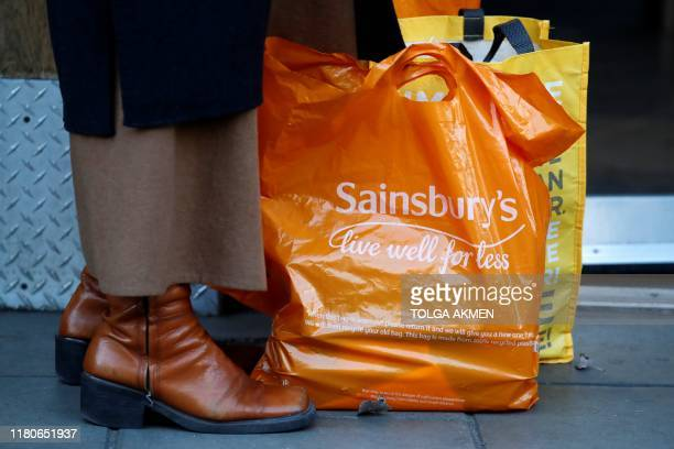 A shopper stands with her purchases in an orange plastic Sainsbury's supermarket store shopping bag in London on November 7 2019 Sainsbury's plunged...
