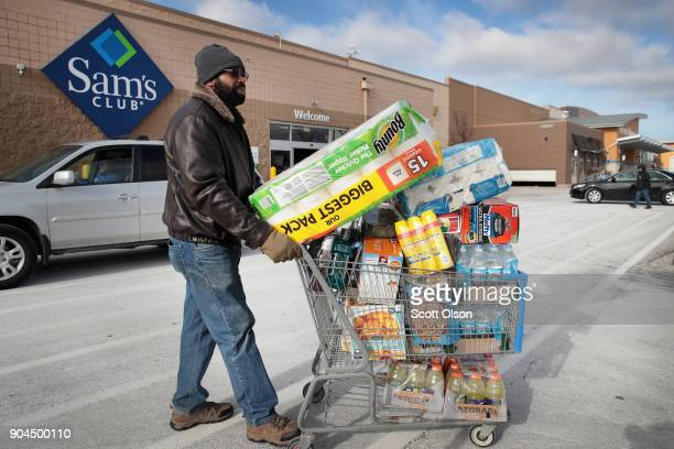 A shopper stocks up on merchandise at a Sam's Club store on January 12 2018 in Streamwood Illinois The store is one of more 60 sheduled to close...