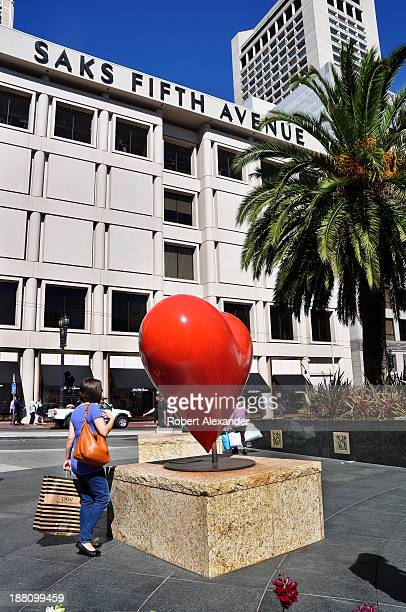 A shopper stops to admire an outdoor sculpture near the Saks Fifth Avenue store located in San Francisco's upscale Union Square shopping district