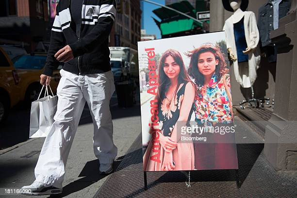 A shopper strolls past an American Apparel Inc store in the shopping district of Soho in New York US on Wednesday Sept 18 2013 Consumers views of the...
