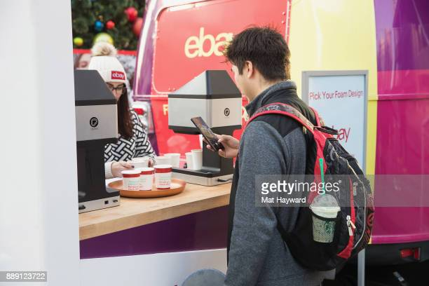 A shopper takes a photo with his phone of the custom hot chocolate during the 'Did You Check eBay' Holiday Airstream tour at Westlake Center Plaza on...