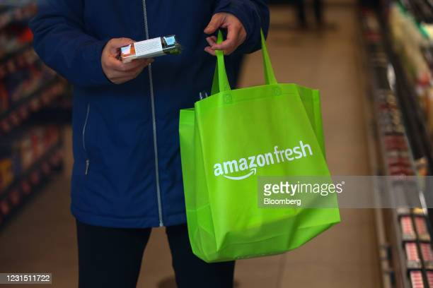 Shopper takes a product off a shelf at the Amazon.com Inc. Amazon Fresh cashierless convenience store in the Ealing area of London, U.K., on...