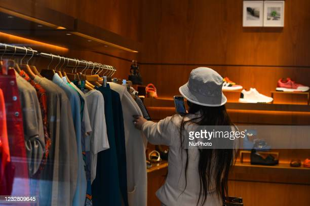 Shopper takes pictures of clothes inside a store in Dublin city center. After five months of strict lockdown, the first stage of defrosting the Irish...