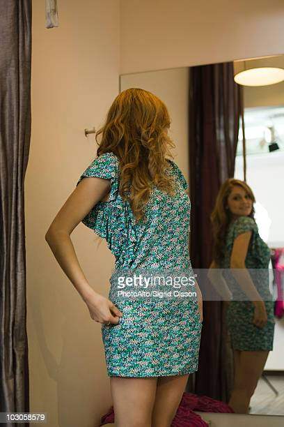 Shopper trying on dress in fitting room