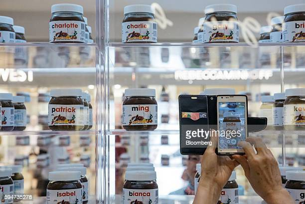 A shopper uses a smartphone to take a photograph of a jar of Ferrero SpA's Nutella hazelnut chocolate spread featuring the name Jade on display at a...