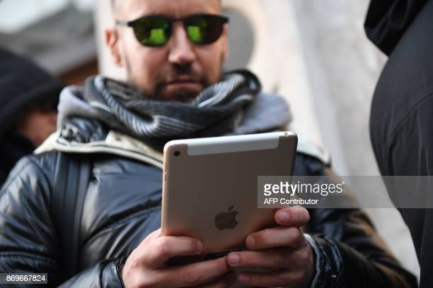 Shopper uses a tablet as he queues outside Apple's Regent Street store in central London on November 3, 2017 waiting for the store to open on the say...