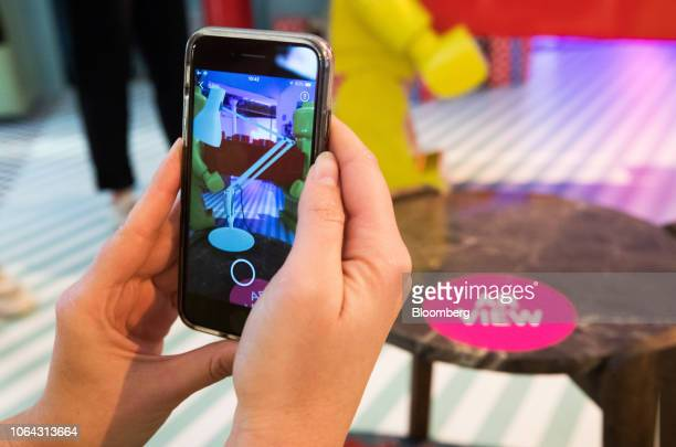 A shopper uses augmented reality smartphone app to simulate a lamp in position on a table at Amazoncom Inc's popup Black Friday store in London UK on...