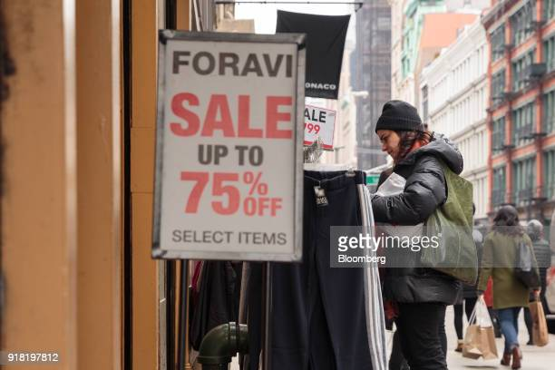 A shopper views a rack of clothing hanging on display for sale in front of a store in the SoHo neighborhood of New York US on Friday Feb 9 2018...