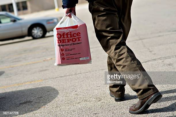 Shopper walks outside an Office Depot Inc. Store in Peoria, Illinois, U.S., on Tuesday, Feb. 19, 2013. Office Depot Inc. And OfficeMax Inc. Are...