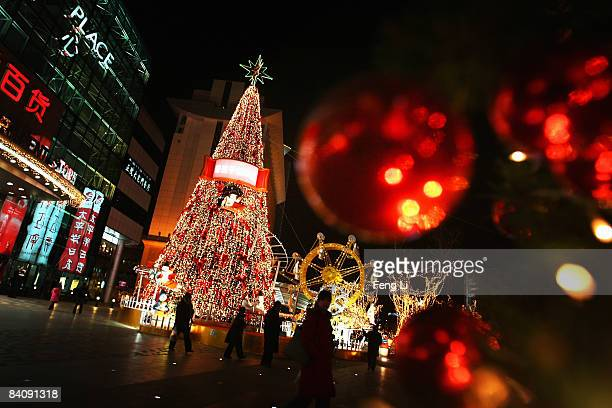 Shopper walks past a Christmas tree installed for the upcoming Christmas celebrations in front of a shopping mall on December 19, 2008 in Beijing,...