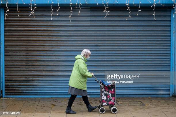 Shopper walks past a closed small business on December 16, 2020 in Port Talbot, Wales. Wales went into a Level 4 lockdown from midnight on December...