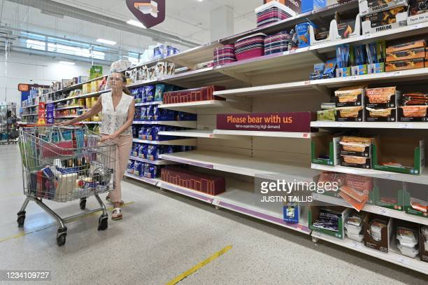 Shopper walks past a sign advising that products are temporarily out of stock is displayed in a supermarket at Nine Elms, south London on July 22,...