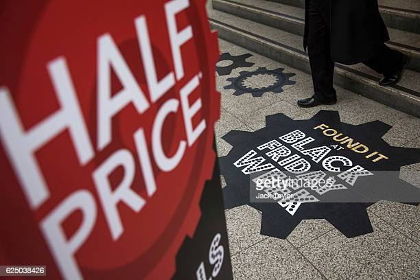 A shopper walks past a sign for Black Friday deals outside a department store on Oxford Street on November 22 2016 in London England British...
