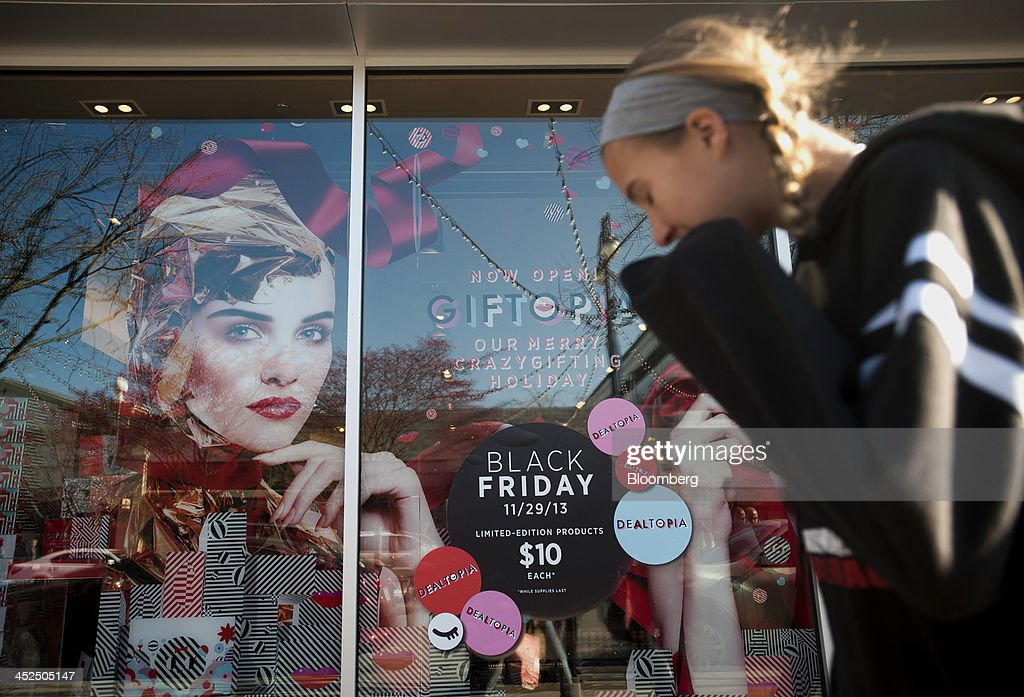 A shopper walks past a storefront at the Easton Towne Center in Columbus, Ohio, U.S., on Friday, Nov. 29, 2013. About 97 million people planned to shop online or in stores on Black Friday, with about 140 million intending to do so yesterday through Sunday, the National Retail Federation said. Photographer: Ty Wright/Bloomberg via Getty Images
