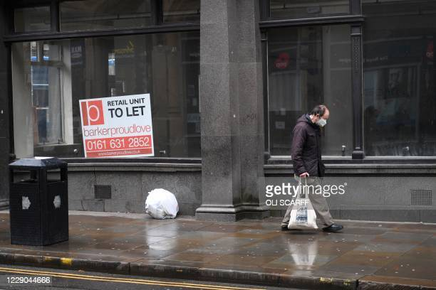 Shopper walks past a 'to let' sign displayed in an empty shop window in Manchester, north west England on October 13 as the number of cases of the...