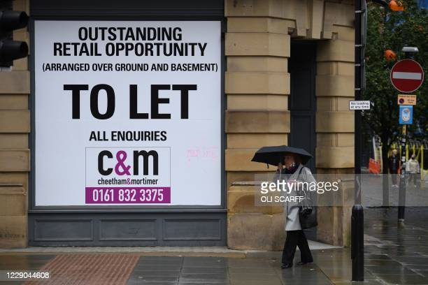 Shopper walks past a 'to let' sign on the exterior wall of business premises in Manchester, north west England on October 13 as the number of cases...