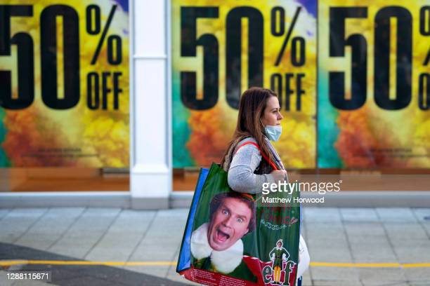 A shopper walks past a Topshop store offering an up to 50% discount on Queen Street on Black Friday on November 27 2020 in Cardiff Wales Restrictions...