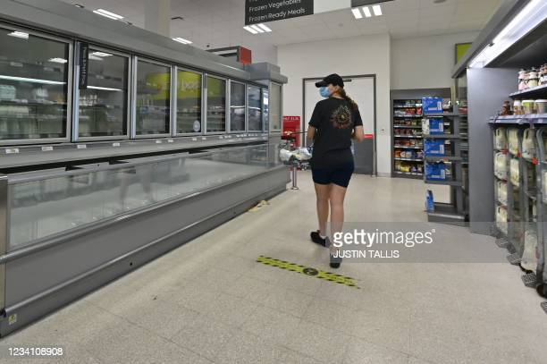 Shopper walks past an empty fridge in a supermarket in Nine Elms, south London on July 22, 2021. - British supermarkets and suppliers warned today of...